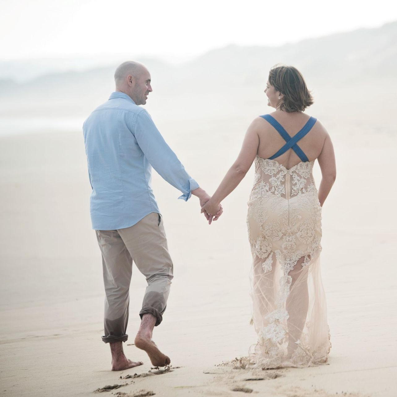 happy wedding couple walking on a beach